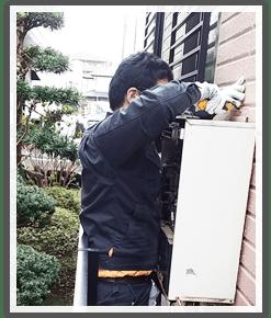 給湯器の本体を撤去する作業スタッフ